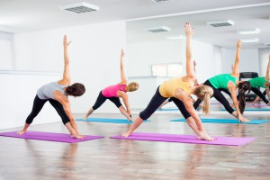 Four girls practicing yoga, Trikonasana / Bikram triangle right