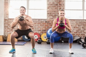 muscular smiling couple with kettlebells