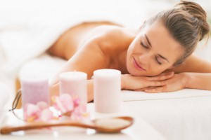 Closeup on spa therapy ingredients and relaxed young woman in background